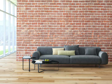 light brown hardwood flooring with a gray couch and a brick wall