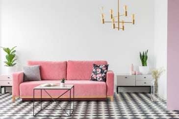 black and white checkered tile flooring in a living room with a pink couch