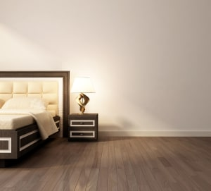 dark brown laminate flooring in a bedroom with a bed