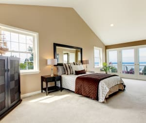 beige wall to wall carpet in a bedroom with a bed