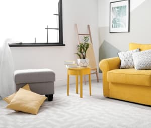 gray patterned carpet in a living room with a yellow couch