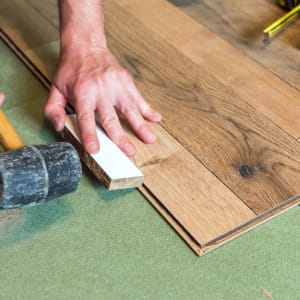 person installing engineered hardwood flooring with a mallet