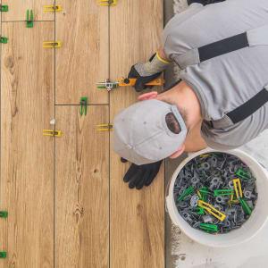 man installing brown wood-look tile flooring