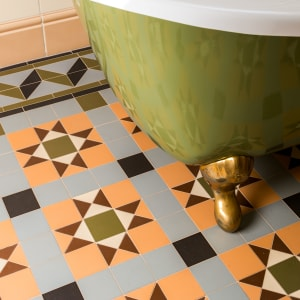 patterned multi-color tile flooring in a bathroom with a green tub